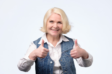 Elderly blonde european woman giving a thumb up and looking at the camera isolated on white background