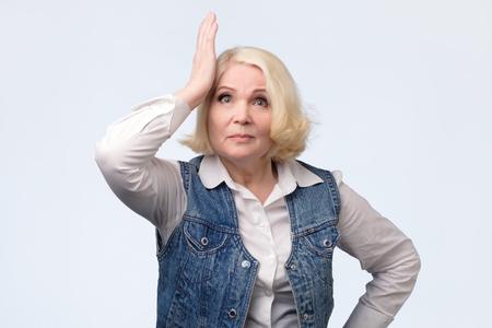Vergeetachtige oudere blonde vrouw die haar hoofd krabt Stockfoto