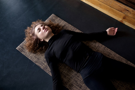 woman practicing in a yoga studio resting in shavasana or corps pose Stock fotó