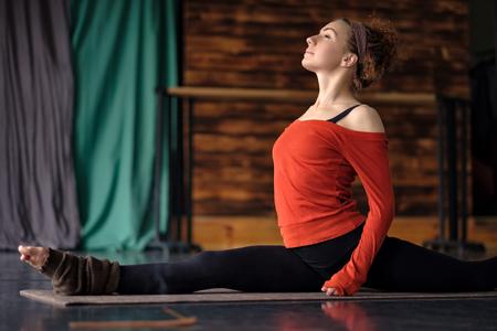 curly woman practicing yoga, doing Monkey God exercise, Splits, Hanumanasana Stockfoto