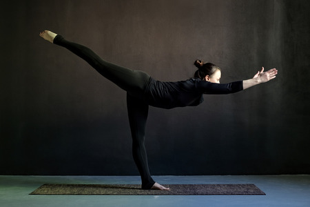 Slim young woman practicing yoga, standing in Warrior posture or Virabhadrasana