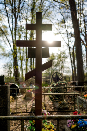 Grave cross on the Orthodox Christian cemetery at sunny day in Russia