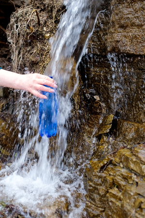 Woman holding a plastic bottle drawing clean water from cold spring. Drinking water source.