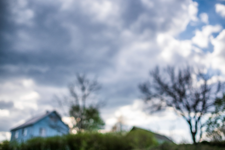 House in the village and cloudy sky. Out of focus