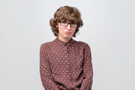 Curly woman frowning being offended and lonely