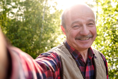 Selfie from handsome senior hispanic man on sunny day.