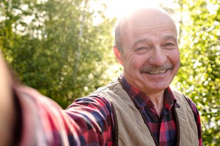 Selfie von einem hübschen älteren hispanischen Mann an einem sonnigen Tag.