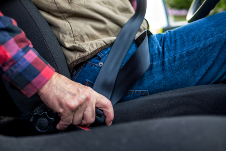 Caucasian man fastening seat belt in car