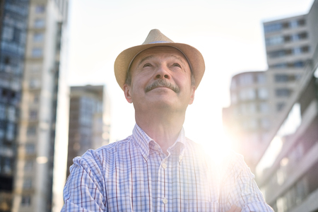 Man in hispanic hat with mustache looking at camera smiling in city