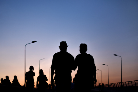 silhouette of couple man and woman walking on sunset