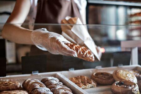 European woman sells in bakery putting bread in paper bag. Stockfoto