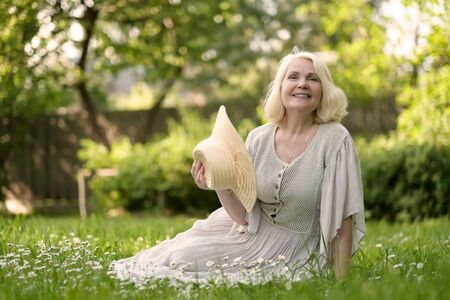 Starsza kobieta w sukience siedzi na trawie w parku