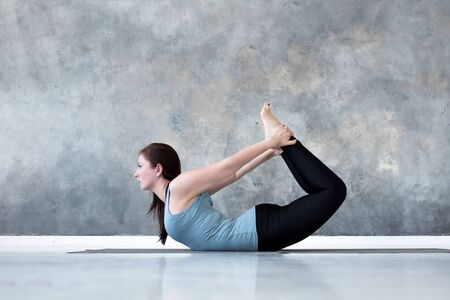 Young woman practicing yoga Bow pose, Dhanurasana