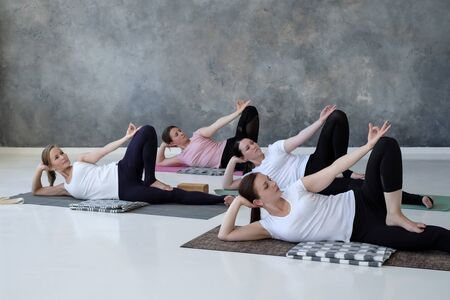 Group of several european women doing yoga posture anantasana. Standard-Bild
