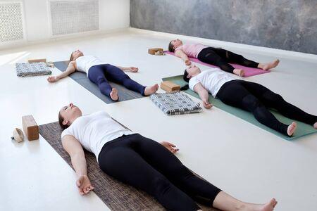 Women practicing yoga lesson, doing Dead Body, Savasana, exercise Corpse pose Stock Photo