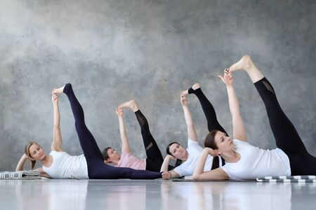 Group of several european women doing yoga posture anantasana. Imagens
