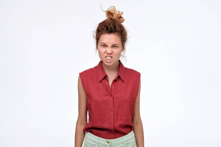 Dissatisfied young woman grimacing, clenching teeth and making angry gestur Stock Photo