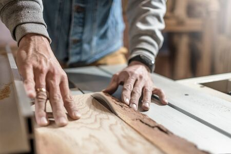 Electric saw cutting wood board. Man working at carpentry workshop