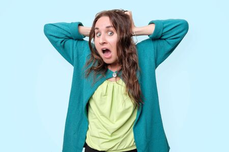 Funny woman is shocked with news holding head with hands in panic. Studio shot on blue background.