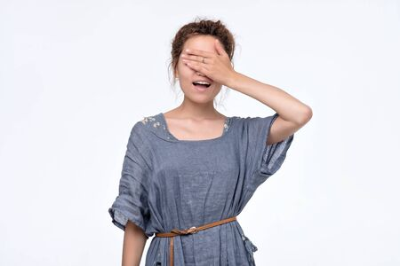 Happy young woman in blue dress covering eyes waiting for gift