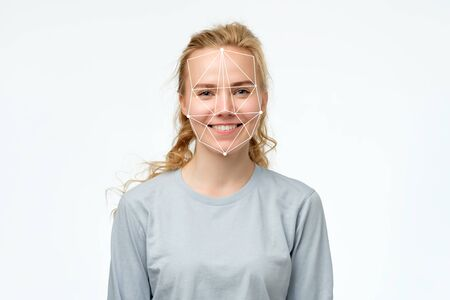 Face recognition in modern technology concept. Portrait of happy blonde girl Imagens