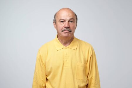 Sad upset mature hispanic guy in yellow pullover looking with guilt and sadness