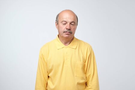 Weary hispanic man in yellow clothes is exhausted. Imagens