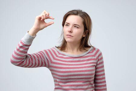 Mujer mostrando algo pequeño y minúsculo con gesto