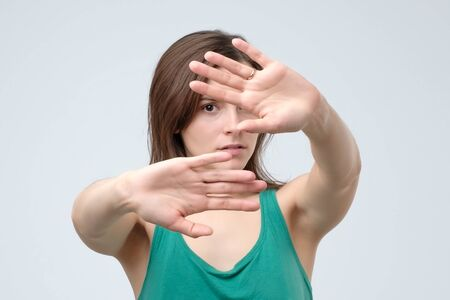 Serious pretty woman making stop hand sign palm gesture