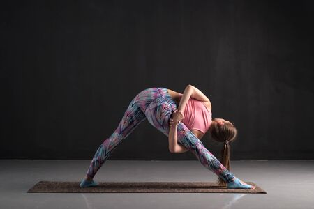 Young woman doing variation of Trikonasana yoga pose Banque d'images