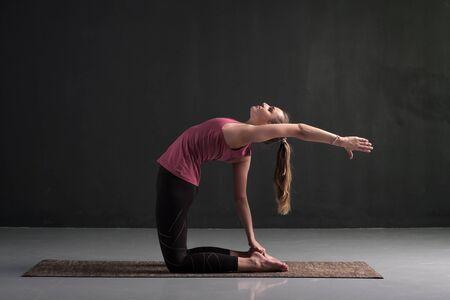 woman yoga instructor doing advanced variation of camel pose or Ustrasana asana