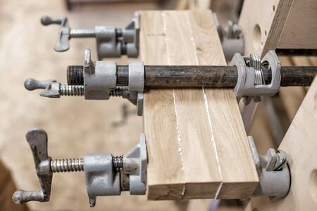 Usando abrazaderas y pegamento para conectar vigas de madera para detalles de muebles. Foto de archivo