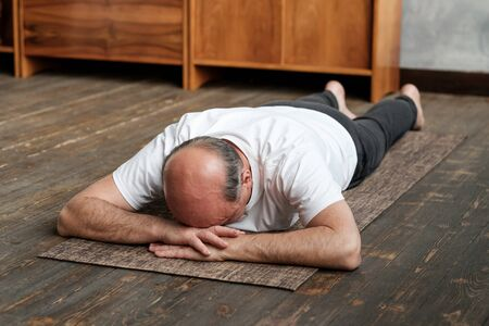 Senior aged man resting after yoga exercise on floor. Sports at home for health. Stock Photo