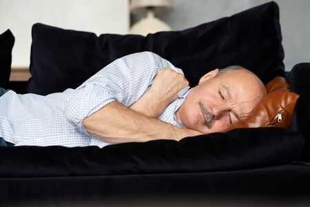 Tired senior hispanic man sleeping on couch, taking afternoon nap 免版税图像