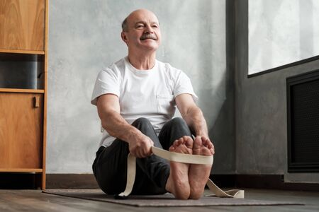 Senior hispanic man sitting in paschimottanasana or Intense Dorsal Stretch pose