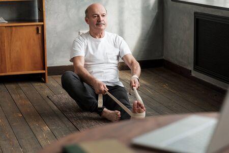 Senior hispanic man sitting in janushirshasana using belt