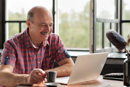 Senior hispanic man smiling looking on laptop screen.