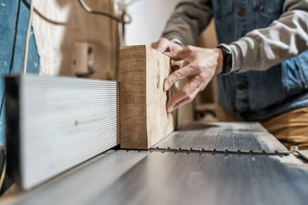 Man making wooden parts for furniture on thickness planer machine.