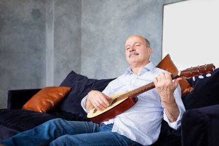Senior hispanic man at home learning to play guitar.