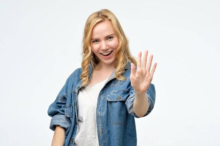 Happy smiling blonde young woman showing five fingers. Stockfoto