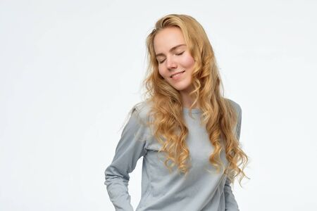 caucasian female looking down with shy smile, being embarrassed Stock Photo