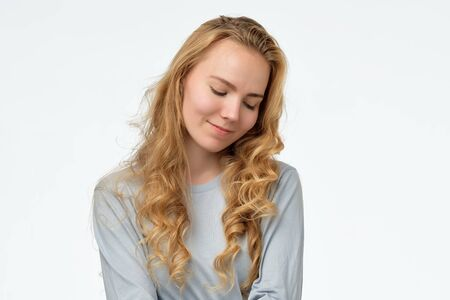 caucasian female looking down with shy smile, being embarrassed