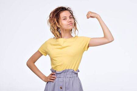 Pretty young asian girl with dreadlocks showing bicep on her arm.