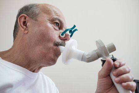 Uomo ispanico senior che testa la funzione respiratoria mediante spirometria