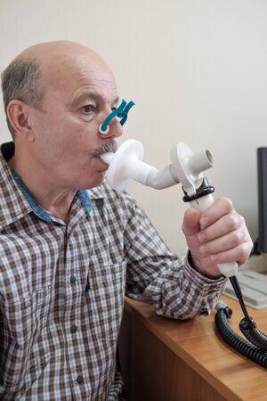 Senior hispanic man man testing breathing function by spirometry