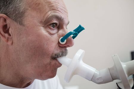 Homme hispanique senior testant la fonction respiratoire par spirométrie