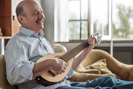 Senior hispanic man playing guitar singing and laughing. Stockfoto