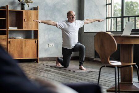 Senior hispanic man standing in warrior yoga pose variation Imagens