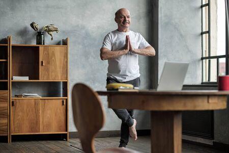 Senior hispanic man standing in one leg yoga balance. Imagens