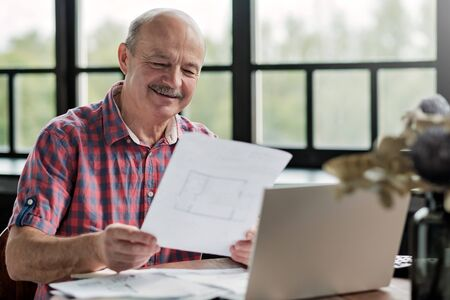 man holding plan of new flat deciding to make an investment